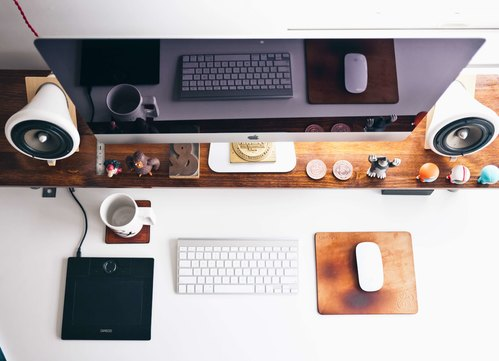 Top view photo of office desk workspace with Apple computer monitor, keyboard, mouse, speakers, and other miscellaneous items. Used for welcome page.