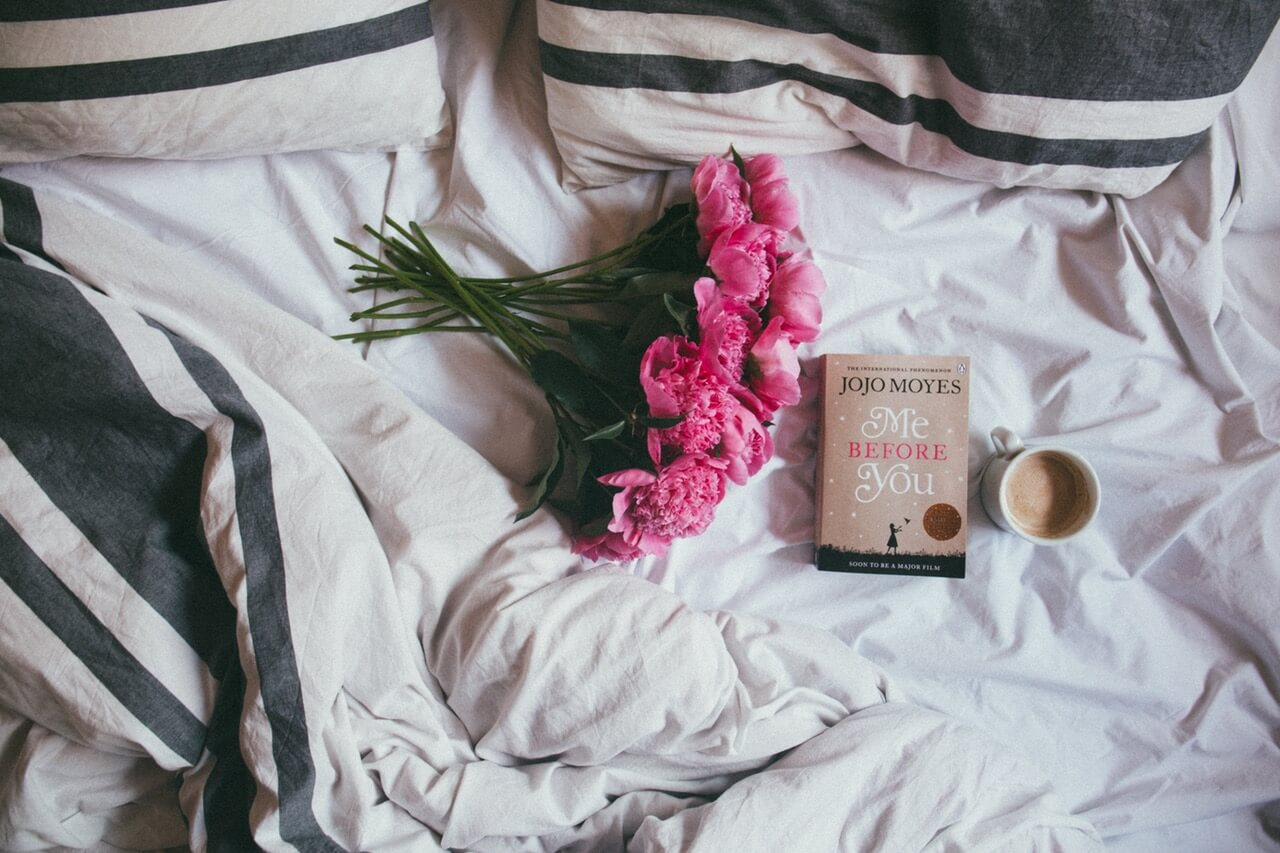 Bright pink flowers, book and warm drink in bed